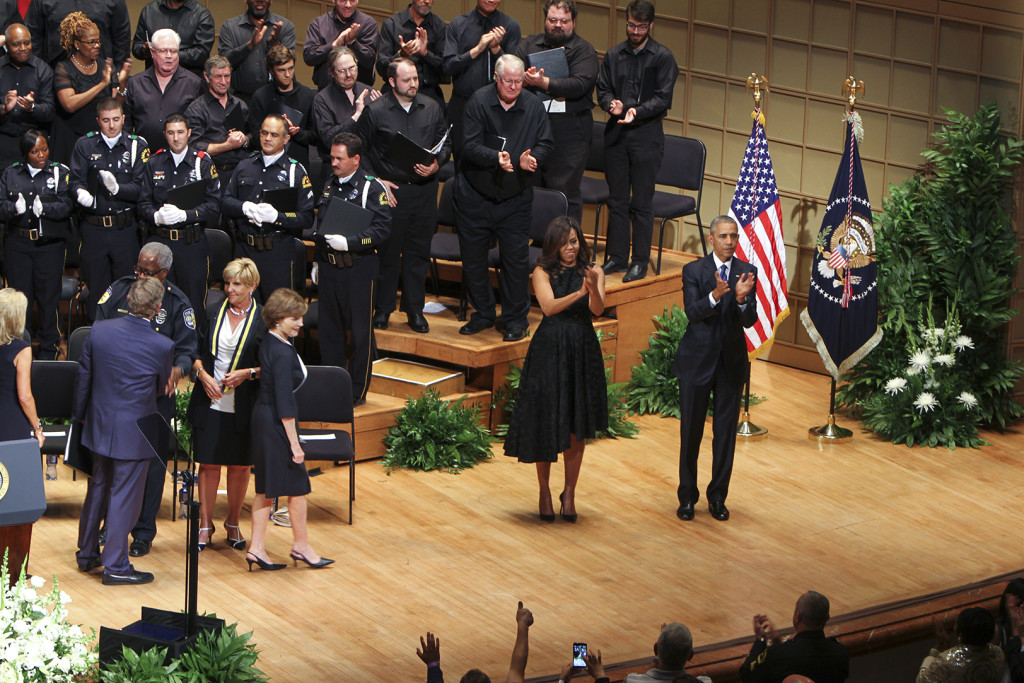"""President Obama and First Lady Michelle Obama attend the memorial service to honor the fallen officers as well as to urge the American people to """"open their hearts and stop the hateful rhetoric"""" that has plagued the nation."""